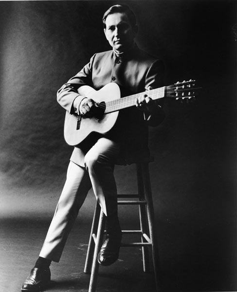 Young musician Willie Nelson sits with his guitar for a studio portrait sans beard in 1960.